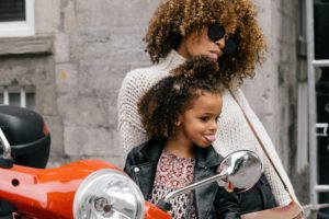 Curly haired mother and daughter making silly faces on a moped