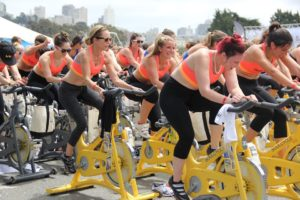 Group of people in orange sports bras cycling