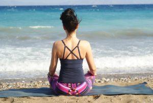 Person meditating at the beach