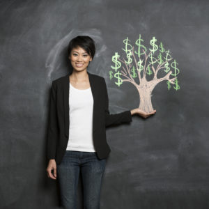 smiling person in front of chalk money tree drawing on blackboard