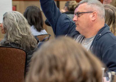 Person in a hoodies raising their hand