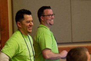two people in green shirts laughing