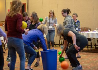 Group of people playing a game tossing bouncy balls into a waste bin