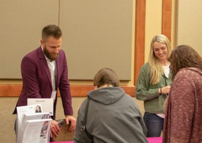 People checking out the Moda Health table