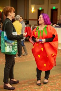 Person dressed in a strawberry costume talking to another person