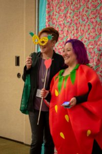 person dressed in an strawberry outfit posing in front of a Photo Booth