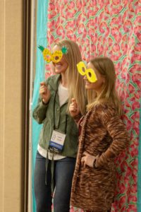 Two people posing at a photo booth with silly props