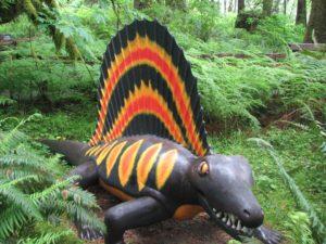 Plastic dinosaur outside amongst some ferns