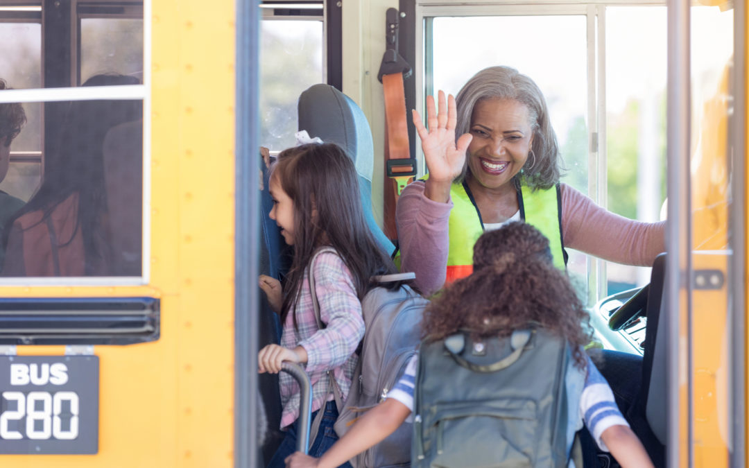 Bus driver high-fiving students on the bus
