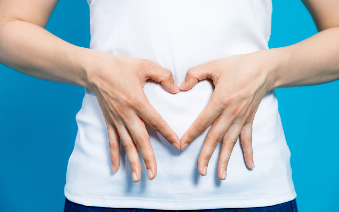 Person making a heart shape with their hands over their stomach