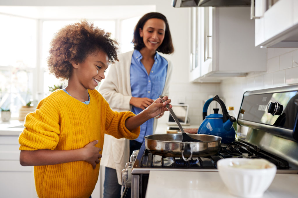 Teenager cooks on the stove with mom's supervision