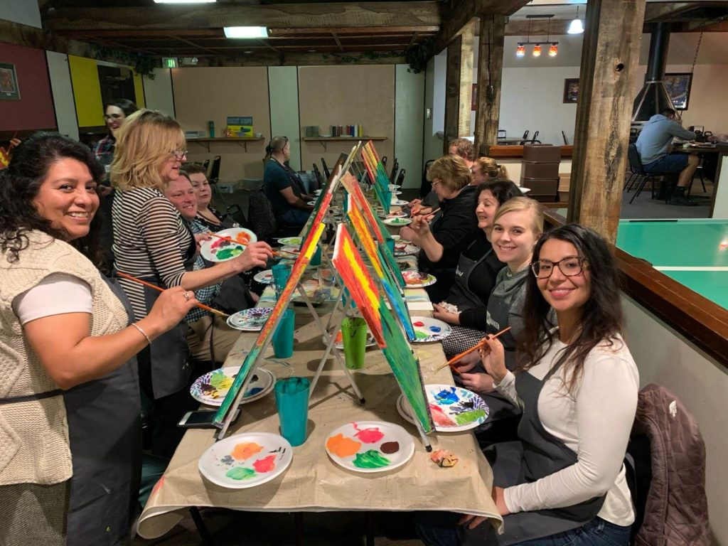 Staff smile at the camera while painting their own canvases at a Paint Night event.